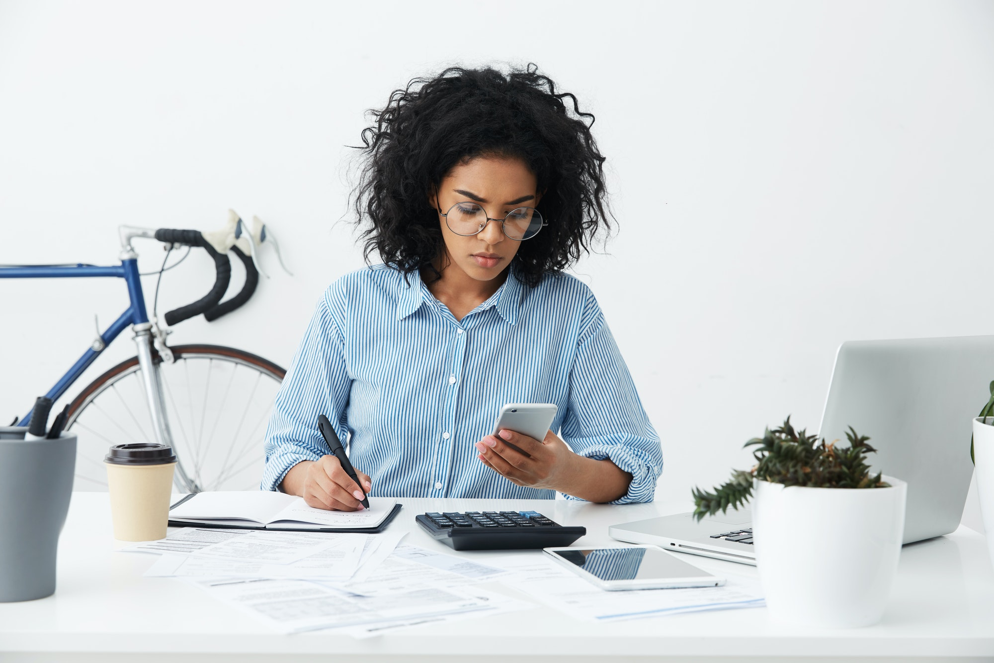 Savings, finances and economy. Concentrated female accountant or banker making calculations at workp