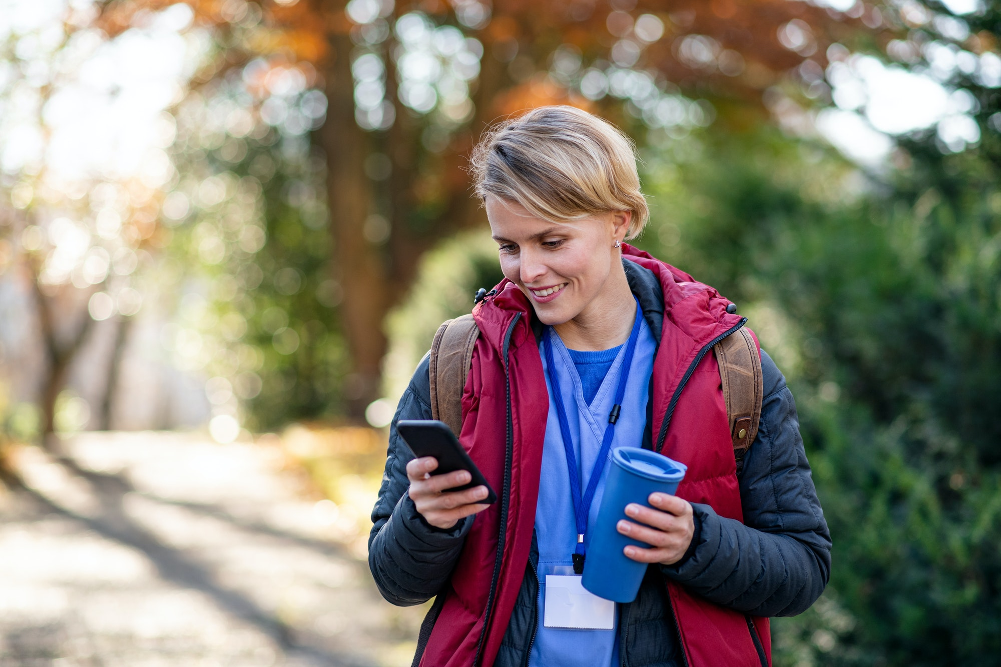 Woman caregiver, nurse or healthcare worker outdoors on the way to work, using smartphone.